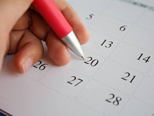 Stock image of a hand holding a pen writing on a desk calendar