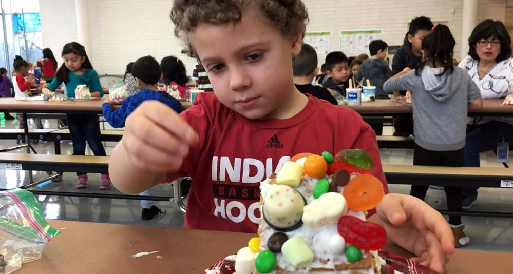 Photo of a Johnson kindergarten student building a gingerbread house