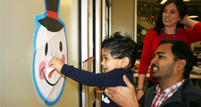 Photo of a father helping a birth-3 student play pin the nose on Frosty