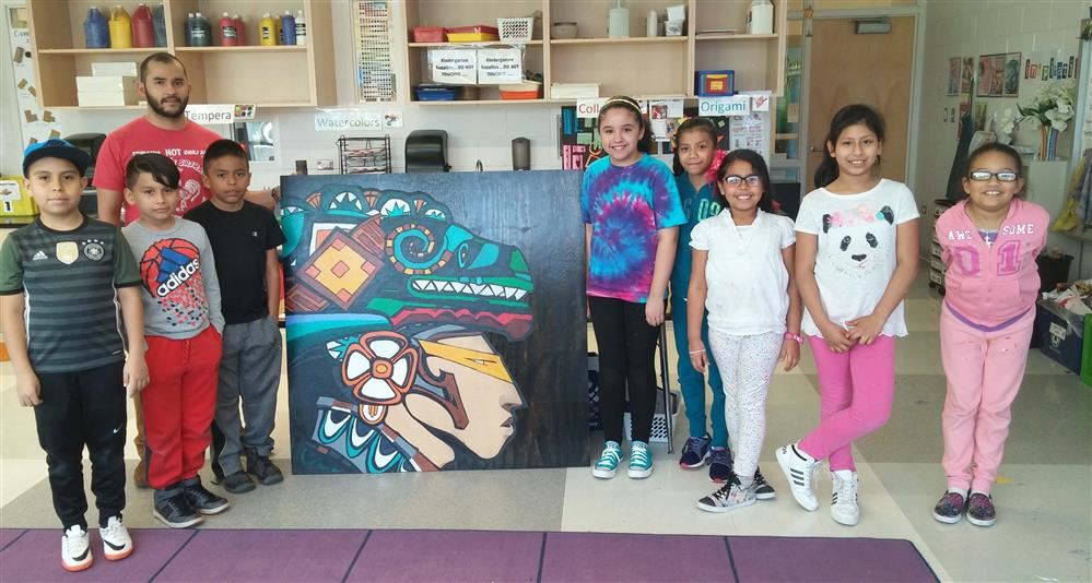 Photof of Johnson students in the Friday Kahlo after-school program posing with art they crreated