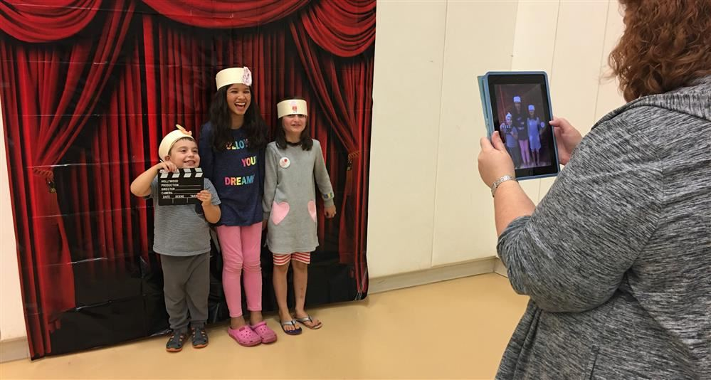 Photo of students posing for photos at a photo booth at Johnson's Literacy Night