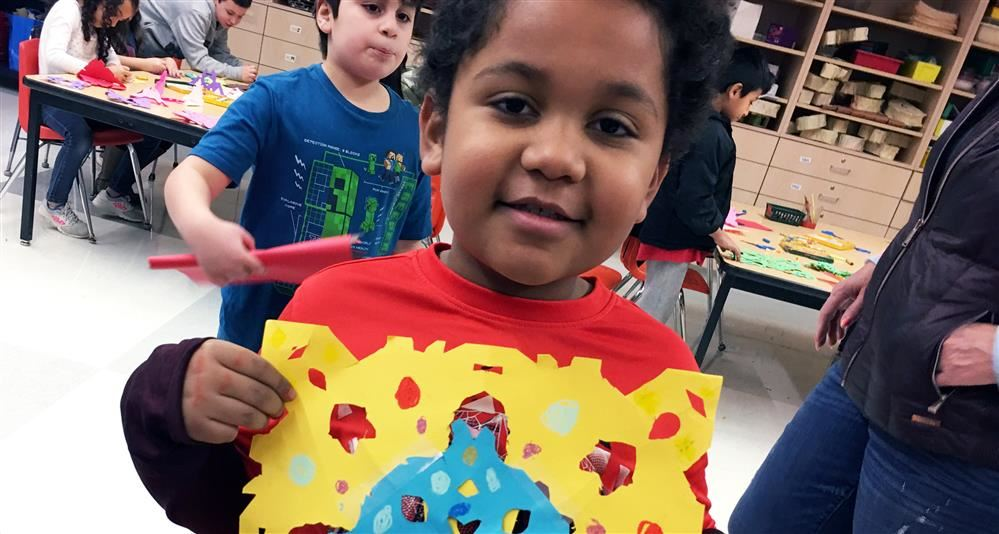 Photo of a Johnson student showing off a snowflake he create in the after-school art program
