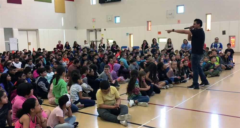 Image of Miguel Rodriguez speaking Johnson students at the Think Kindness assembly.