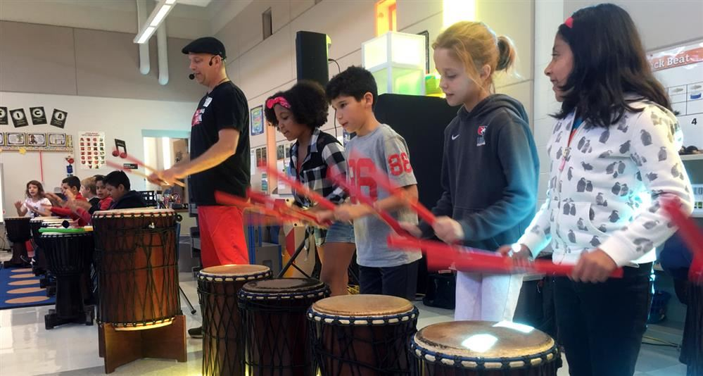 Photo of Johnson students drumming during the Dancing Drum program