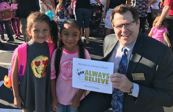 Photo of Dr. Stelter and students holding an ALWAYS BELIEVE sign